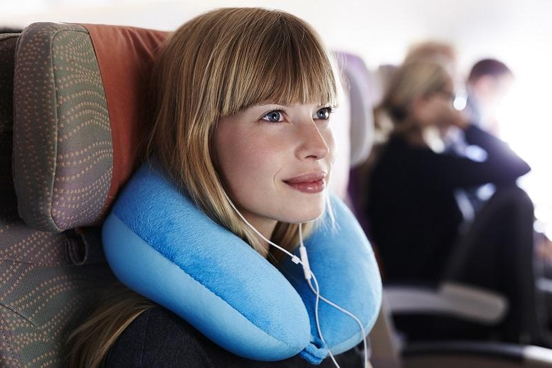 cô gái tóc vàng đeo gối cổ chữ u màu xanh da trời